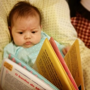 Manu curiosa com o livro que comprei para ela na Bienal de SP.